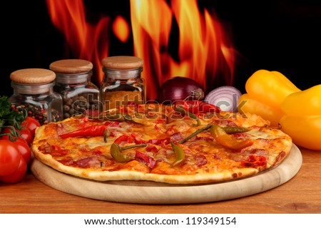 Tasty pepperoni pizza with vegetables on wooden board on flame background