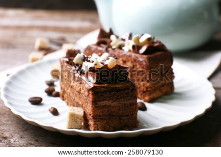 Tasty piece of chocolate cake with lump sugar and coffee beans on wooden table background - stock photo