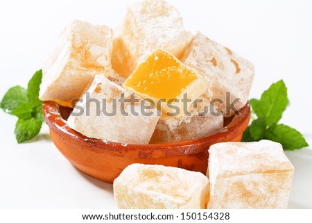 Tasty pieces of orange turkish delight in a ceramic bowl - stock photo