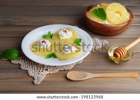 Tasty pineapple with cottage cheese on  wooden table - stock photo