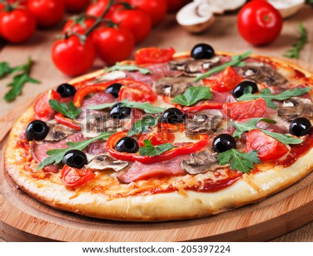 Tasty pizza and fresh ingredients on the table  - stock photo