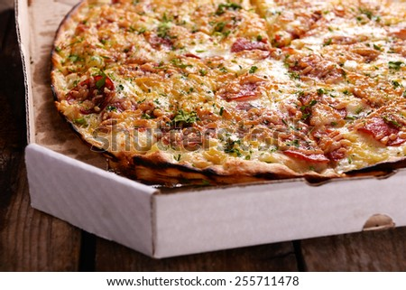 Tasty pizza in box on wooden background - stock photo