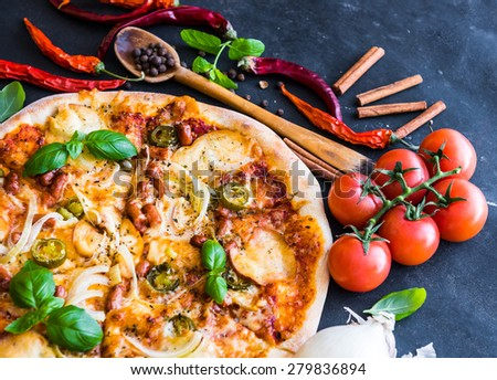 tasty pizza on a black background with spices and vegetables - stock photo