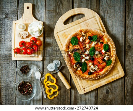 Tasty pizza on a wooden board. Veggie a pizza with ingridients . - stock photo
