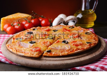 Tasty pizza on table on dark red background
