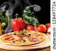 Tasty pizza on  wooden plate close up - stock photo