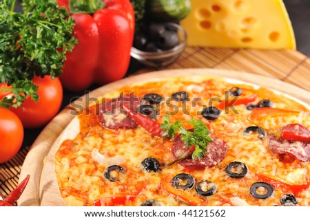 Tasty pizza on  wooden plate close up