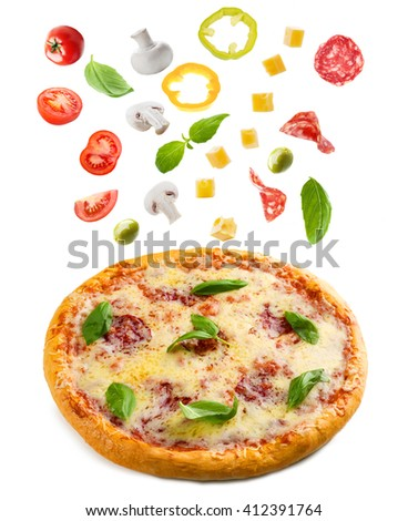Tasty pizza with falling vegetables and pieces of salami, isolated on white - stock photo