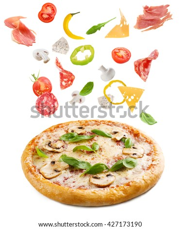 Tasty pizza with falling vegetables, pieces of salami and jamon, isolated on white - stock photo