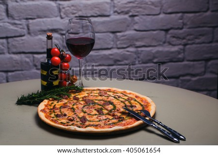 Tasty pizza with meat, cheese and pesto and glass of red wine