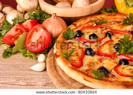 tasty pizza with olives and vegetables on a wooden background