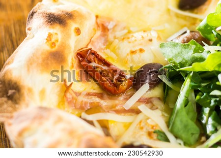Tasty pizza with rikula, smoked ham pieces, bacon and mozzarella - stock photo