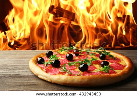 Tasty pizza with salami and olives on wooden table against fire flame background - stock photo