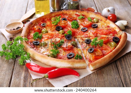 Tasty pizza with sausage, vegetables and chili pepper on wooden table background - stock photo