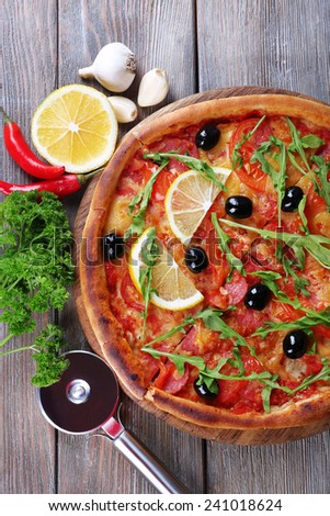 Tasty pizza with spices and round knife on board and wooden table background - stock photo