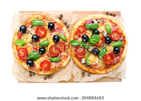 Tasty pizza with vegetables and basil on cutting board close up