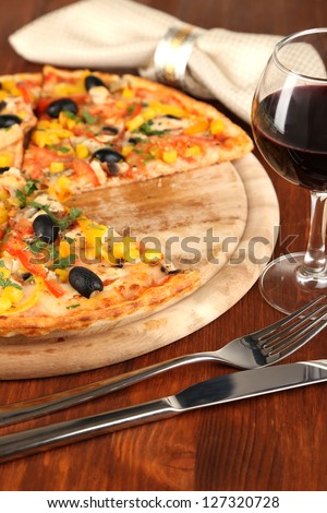 Tasty pizza with wine on wooden table close-up - stock photo