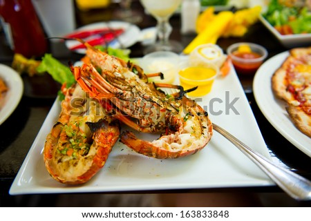 Tasty plate of seafood meal on it with fresh cooked lobster flavored with garden green - stock photo
