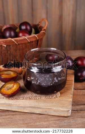 Tasty plum jam in jar and plums on wooden table on wooden background - stock photo