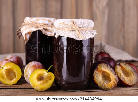 Tasty plum jam in jars and plums on wooden table on wooden background - stock photo