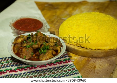 Tasty polenta with meat. Traditional Romanian dish made from beef and pork served with  polenta. Polenta and stew - stock photo