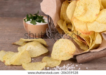 Tasty potato chips in metal basket  on wooden table - stock photo