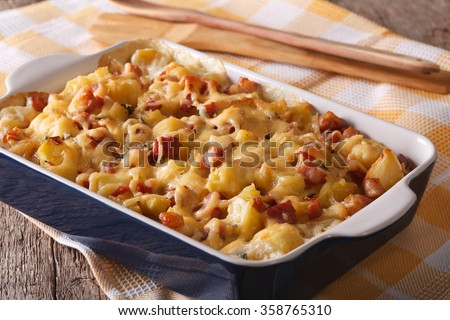Tasty potatoes with bacon and cheese close up in baking dish. horizontal - stock photo