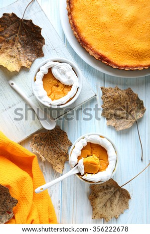 Tasty pumpkin pie in bowl on a blue wooden table - stock photo