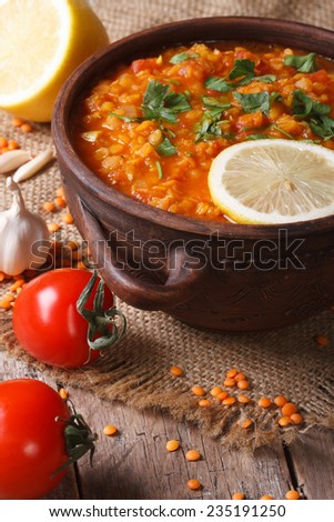 Tasty red lentil soup with vegetables close-up on the table. vertical, rustic style