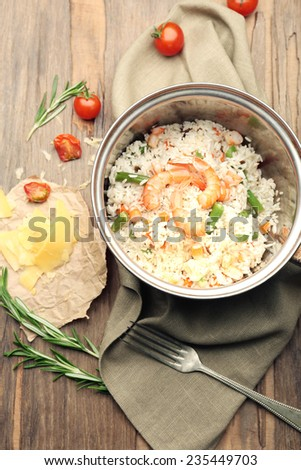 Tasty rice in pan on wooden table