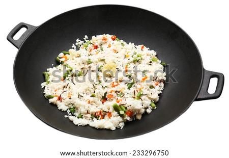 Tasty rice preparing in wok, isolated on white - stock photo