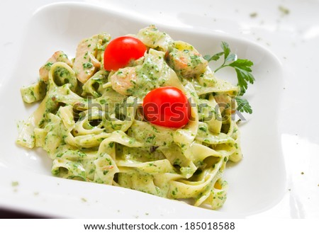 Tasty rich Pesto Chicken tagliatelle pasta with cherry tomato and fresh parsley - stock photo