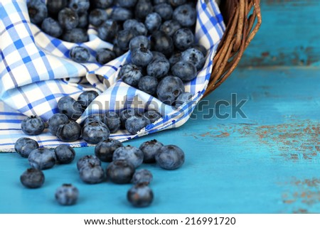 Tasty ripe blueberries in basket, on wooden table - stock photo