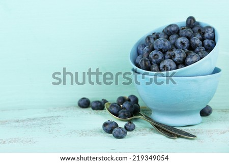 Tasty ripe blueberries in cups, on wooden table - stock photo