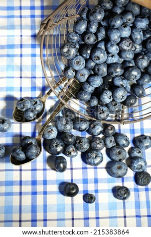 Tasty ripe blueberries in metal basket, on tablecloth background - stock photo