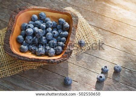 Tasty ripe blueberries with mint in bowl on table close up. Blueberries in a bowl on a wooden table.