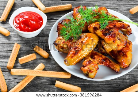 tasty roasted Ginger and honey sticky chicken wings on a white dish decorated with dill, tomato sauce in a gravy boat and bread sticks on an old wooden table,  top view, close-up - stock photo