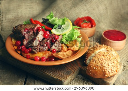 Tasty roasted meat with cranberry sauce, salad and roasted vegetables on plate, on sackcloth background - stock photo