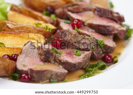 Tasty roasted pork meat with potatoes - stock photo