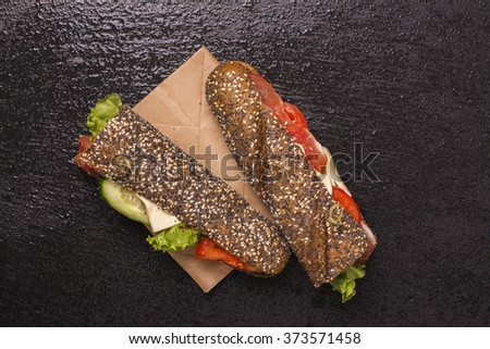 Tasty rye bread sandwiches with ham, cheese and vegetables over black stone background. Top view. Selective focus - stock photo