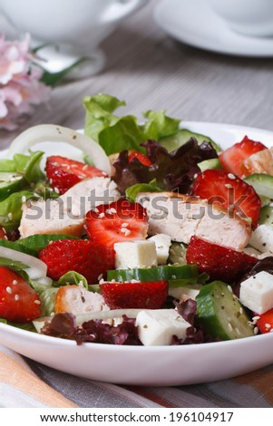 Tasty salad of strawberries with chicken and vegetables close-up. vertical