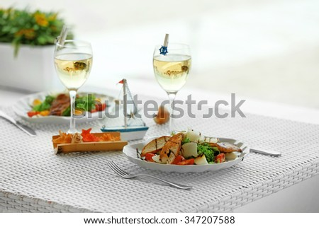 Tasty salad on white served table, outdoors - stock photo