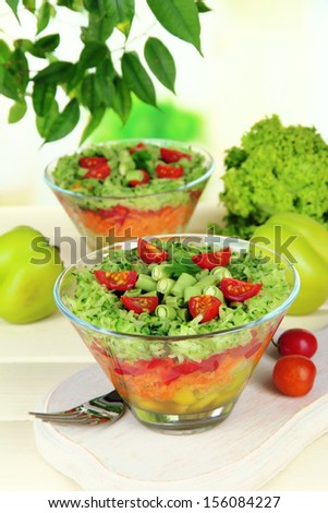 Tasty salad with fresh vegetables on wooden table