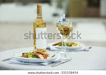Tasty salad with wine on white served table - stock photo