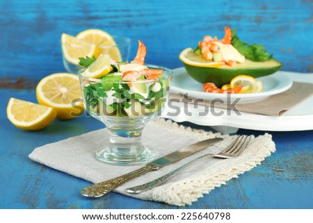 Tasty salads with shrimps and avocado in glass bowl and on plate, on wooden background