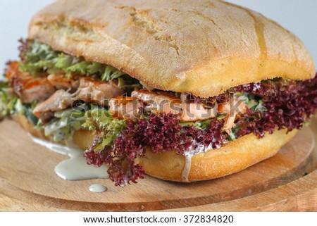 Tasty salmon steak sandwich in a ciabatta with lettuce, Marie Rose sauce and lemon juice - stock photo