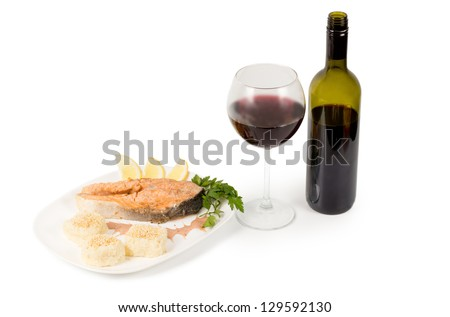 Tasty salmon steak served with an unlabelled bottle and full glass of red wine - stock photo