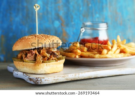 Tasty sandwich on cutting board, on color wooden background. Unhealthy food concept - stock photo