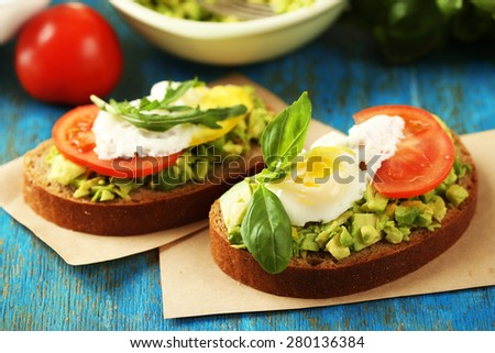 Tasty sandwich with egg, avocado and vegetables on paper napkin, on color wooden background - stock photo