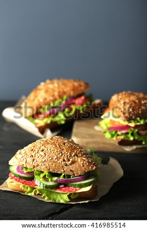 Tasty sandwiches with salami on a black wooden background - stock photo